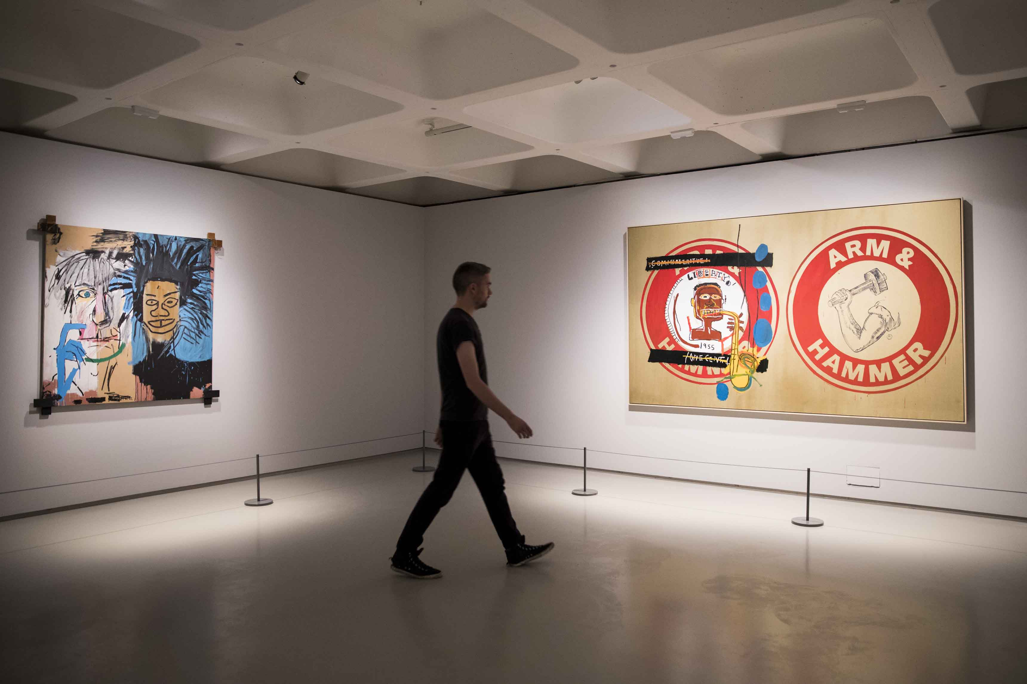 Basquiat: Boom For Real Installation view Barbican Art Gallery 21 September 2017 – 28 January 2018 © Tristan Fewings / Getty Images Artworks (left to right): Jean-Michel Basquiat Dos Cabezas, 1982 Private collection, © The Estate of Jean-Michel Basquiat. Licensed by Artestar, New York. Jean-Michel Basquiat and Andy Warhol Arm and Hammer II, 1984 Acrylic on canvas Guarded by Bischofberger, Männedorf-Zurich, Switzerland © The Estate of Jean-Michel Basquiat. Licensed by Artestar, New York. Courtesy Galerie Bruno Bischofberger, Männedorf-Zurich, Switzerland