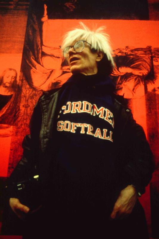 """Andy Warhol devant """"The Last Supper (Red)"""" (1986), à l'inauguration de """"Andy Warhol – Il Cenacolo"""" au Palazzo delle Stelline, à Milan, le 22 janvier 1987. © Archivio Garghetti. Courtesy Gagosian."""