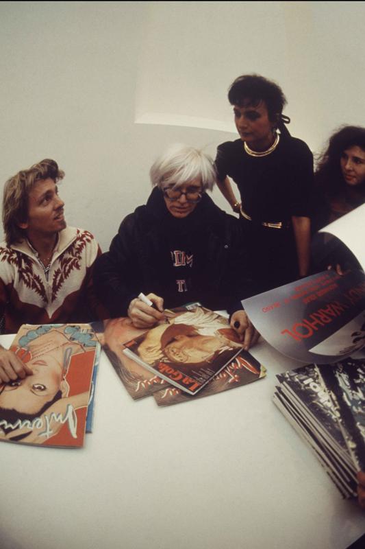 """Andy Warhol dédicaçant des exemplaires de """"Interview magazine"""" à l'inauguration de """"Andy Warhol – Il Cenacolo"""" au Palazzo delle Stelline, à Milan, le 22 janvier 1987. © Archivio Garghetti. Courtesy Gagosian."""