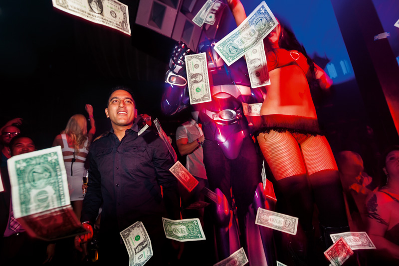 "Short caption: Marquee nightclub, Las Vegas, 2012. © 2017 Lauren Greenfield (page 457, upper image) Extended caption: A VIP guest ""makes it rain"" with hundreds of dollar bills on a sold-out Saturday night at Marquee, routinely ranked as one of the top-grossing nightclubs in the United States, Las Vegas, 2012. Hip-hop artist Fat Joe brought the practice into mainstream clubs with his hit song of the same name. Photograph and text © 2017 Lauren Greenfield (page 457, upper image)"