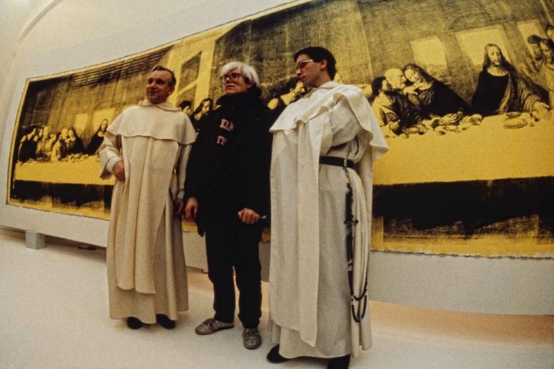 """Andy Warhol devant """"The Last Supper (Yellow)"""" (1986),  à l'inauguration de """"Andy Warhol – Il Cenacolo"""" au Palazzo delle Stelline, à Milan, le 22 janvier 1987.. © Archivio Garghetti. Courtesy Gagosian."""