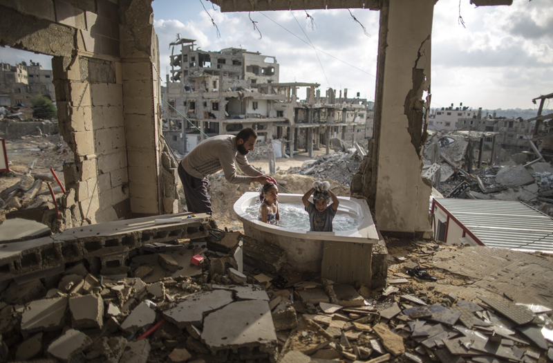 Wissam Nassar, Salem bathes his 5 year-old daughter and niece in the only surviving piece of his wartorn house in Gaza. 2015. © Wissam Nassar