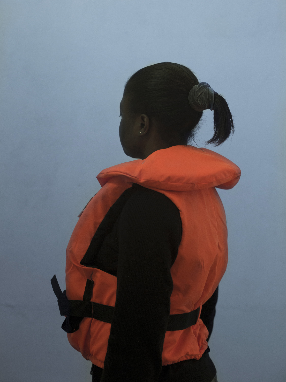 Une jeune migrante essaie le gilet de sauvetage © Myriam Meloni qu'elle devra mettre pour traverser la Méditerranée. #portrait Environ 3371 personnes y ont trouvé la mort en 2015.