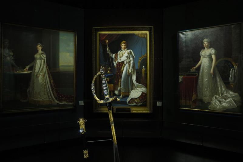 """Épée consulaire dite """"Épée du sacre"""" de Napoléon 1er, de Marie-Étienne Nitot, joaillier, Nicolas-Noël Boutet, armurier, et Jean-Baptiste-Claude Odiot, orfèvre, 1802. Or, jaspe sanguin, pierres d'inscrustation, écaille, acier et cuir. Portée par Napoléon 1er le jour de son sacre, elle est ici présentée devant la toile """"L'Empereur Napoléon 1er en costume de sacre"""" de François Gérard (1806)."""