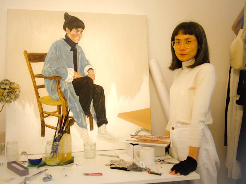 """Jiab Prachakul dans son atelier. """"Seated Girl in Blue Cape"""" (2019), acrylique et l'huile sur toile, 100 x 100 cm. Courtesy of the artist."""