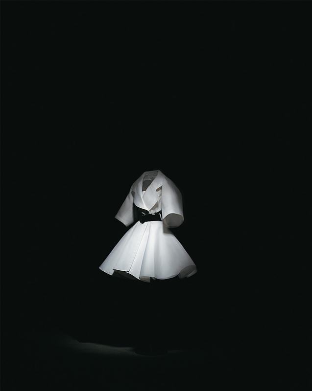 Trench-coat Forcément en gazar blanc fermé par une large ceinture en cuir verni noir, porté sur une robe en shantung blanc, haute couture printemps-été 1991, Rendez-vous d'amour. Collection Dior Héritage, Paris. Photo : Laziz Hamani