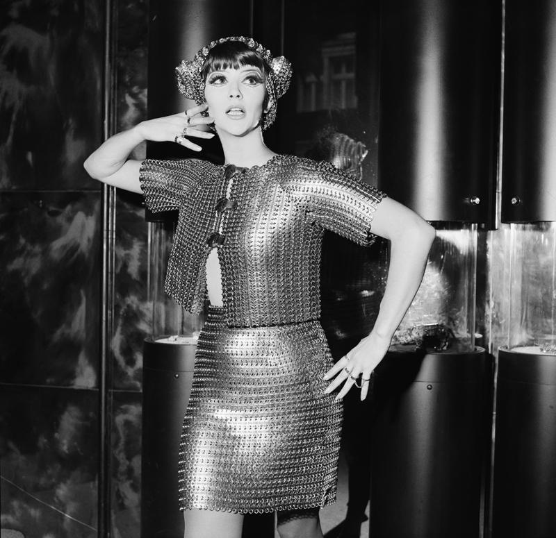 Jackie Bowyer porte un boléro en cotte de mailles en argent avec une mini-jupe assortie de Paco Rabanne, le 7 novembre 1967. Elle le porte lors de l'ouverture de la nouvelle bijouterie Jones à Brompton Arcade, Knightsbridge, Londres. ©Peter King / Fox Photos / Getty Images