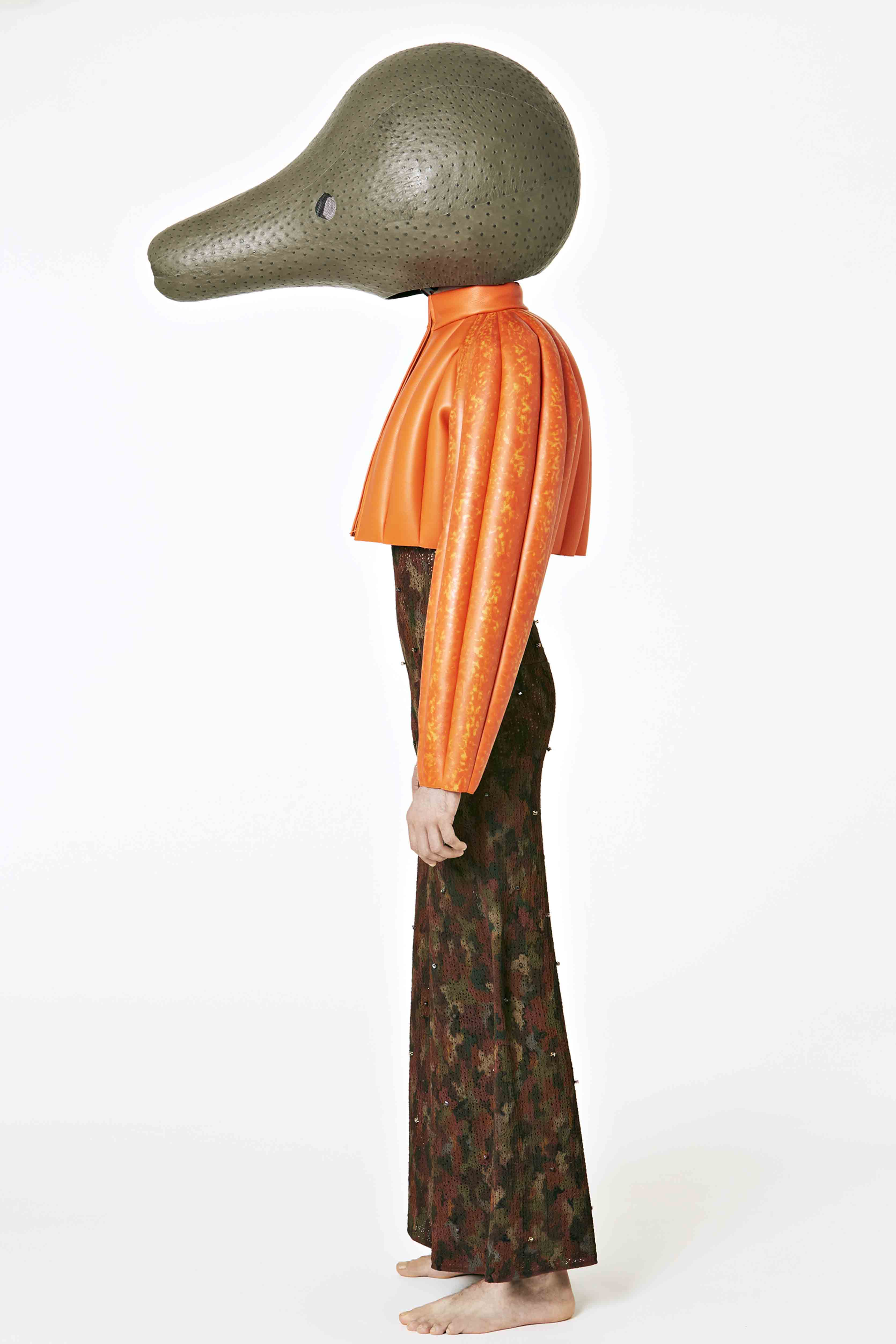 Loewe -Fiber glass head covered in dark grey ostrich leather. Orange handpainted leather bolero.  Knitted tracksuit in vegetal hand painted texture with Swarovski hand stitched stone.