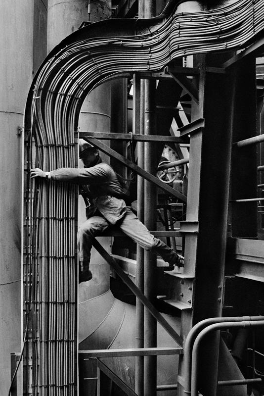 Un ouvrier répare des tuyaux qui font partie du système de câblage électronique autour du haut fourneau numéro 4. Dunkerque. France, 1987.