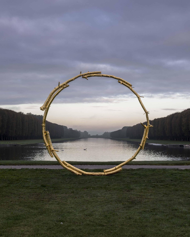 Ugo Rondinone évoque l'astre solaire à l'orée du bassin d'Apollon. L'ensemble de l'œuvre de l'artiste est alimenté par une médiation entre la nature et le cycle de la vie, le Roi Soleil est ici un cercle illusoire alors que l'hiver survient. / Ugo Rondinone, the sun, 2017 Bronze doré Courtesy de l'artiste, kamel mennour (Paris/Londres), Barbara Gladstone Gallery (New York/ Bruxelles)