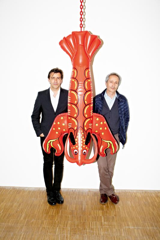 Yannick Alléno (à gauche) et Bernard Blistène (à droite) lors du décrochage de l'exposition Jeff Koons au Centre Pompidou devant l'oeuvre Lobster [Homard] (2003), en aluminium polychrome et chaîne en acier, 147 x 94 x 43,5 cm (©Jeff Koons/Collection de l'artiste).