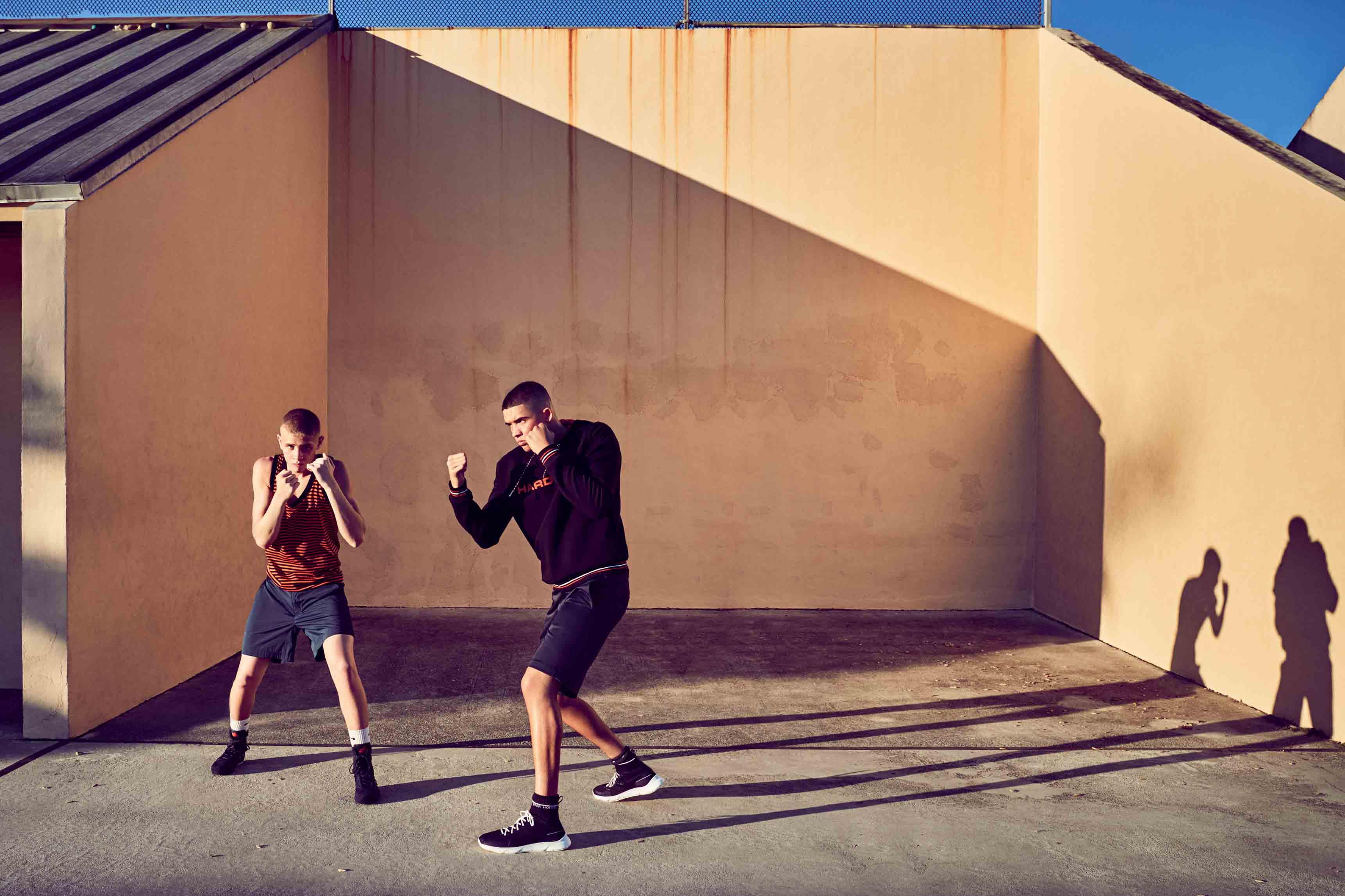 À gauche : débardeur en jersey de coton et bermuda en gabardine de coton, Dior Homme. Chaussettes, Nike. Sneakers, Adidas. À droite : sweat-shirt en jersey de coton, bermuda en satin de coton et sneakers, Dior Homme. Chaussettes, Nike.