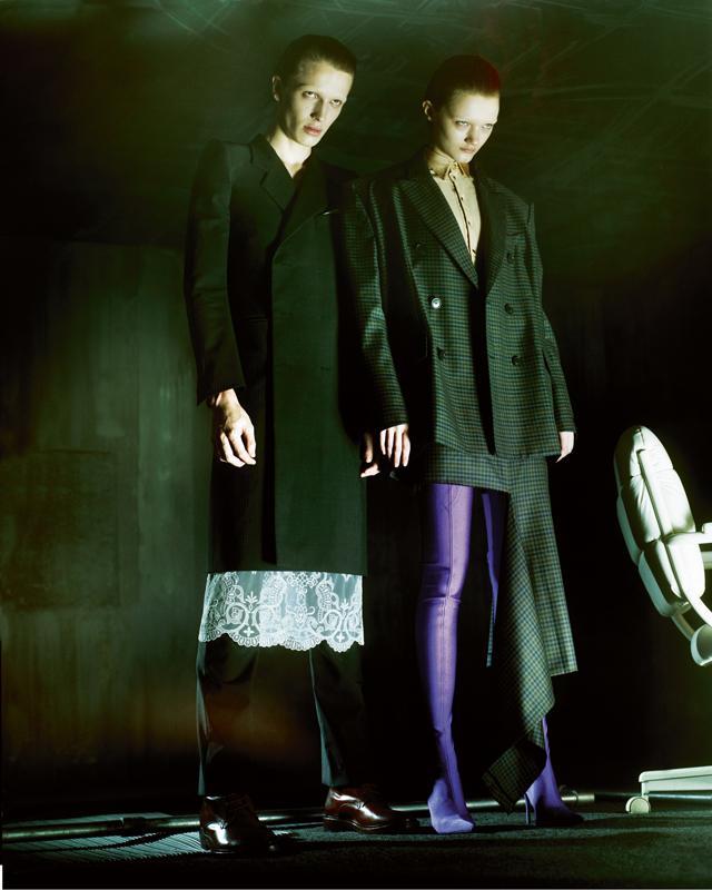 À droite, elle : veste et jupe asymétrique en laine prince-de-galles, chemise en spandex et cuissardes, BALENCIAGA. À gauche, lui : manteau et pantalon en laine, tablier en dentelle et boots, BALENCIAGA.