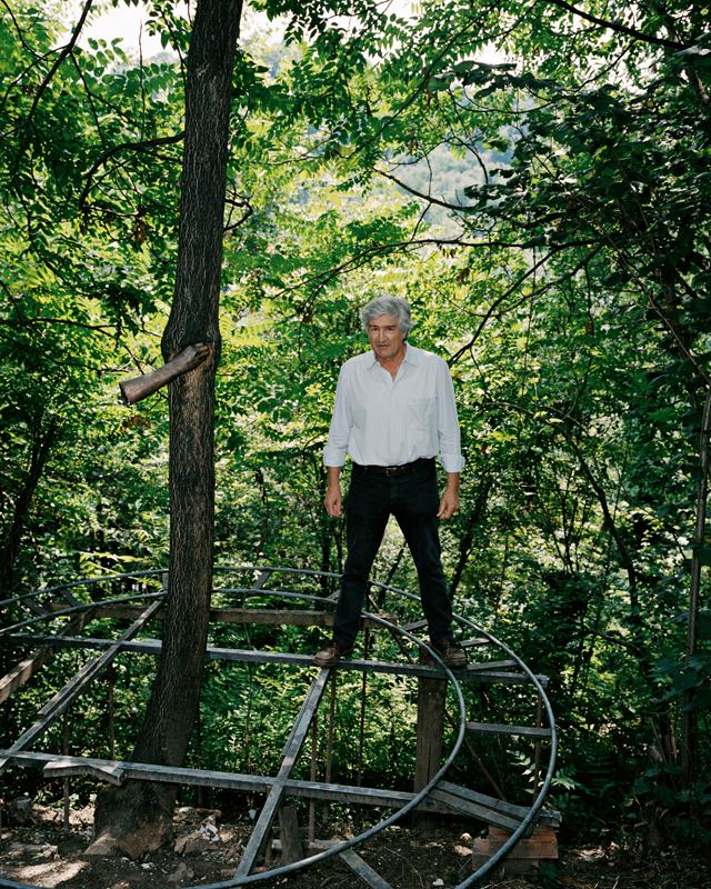 Giuseppe Penone pose à côté de son œuvre inaugurale de 1968, reproduite dans sa forêt près de Turin. Il a maintenu le tronc d'un arbre avec sa main, moulée en acier. La croissance lente de l'arbre est marquée par cette présence, le tronc adaptant son parcours.