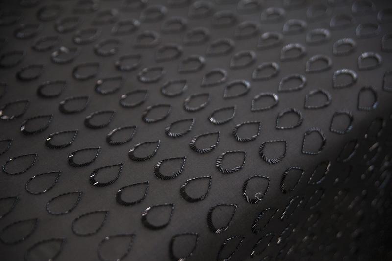 Étape de confection des broderies d'une robe de la collection Paris-Hambourg. Les gouttes d'organza noir, rappelant l'eau du port d'Hambourg, sont ourlées de perles.