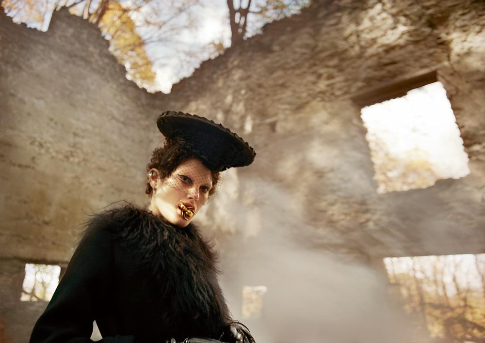 Coat, MAJE. Hat, HEATHER HUEY. Veil, JENNIFER BEHR. Earings, MARIA TASH. Earring (in the mouth), NEW YORK VINTAGE.