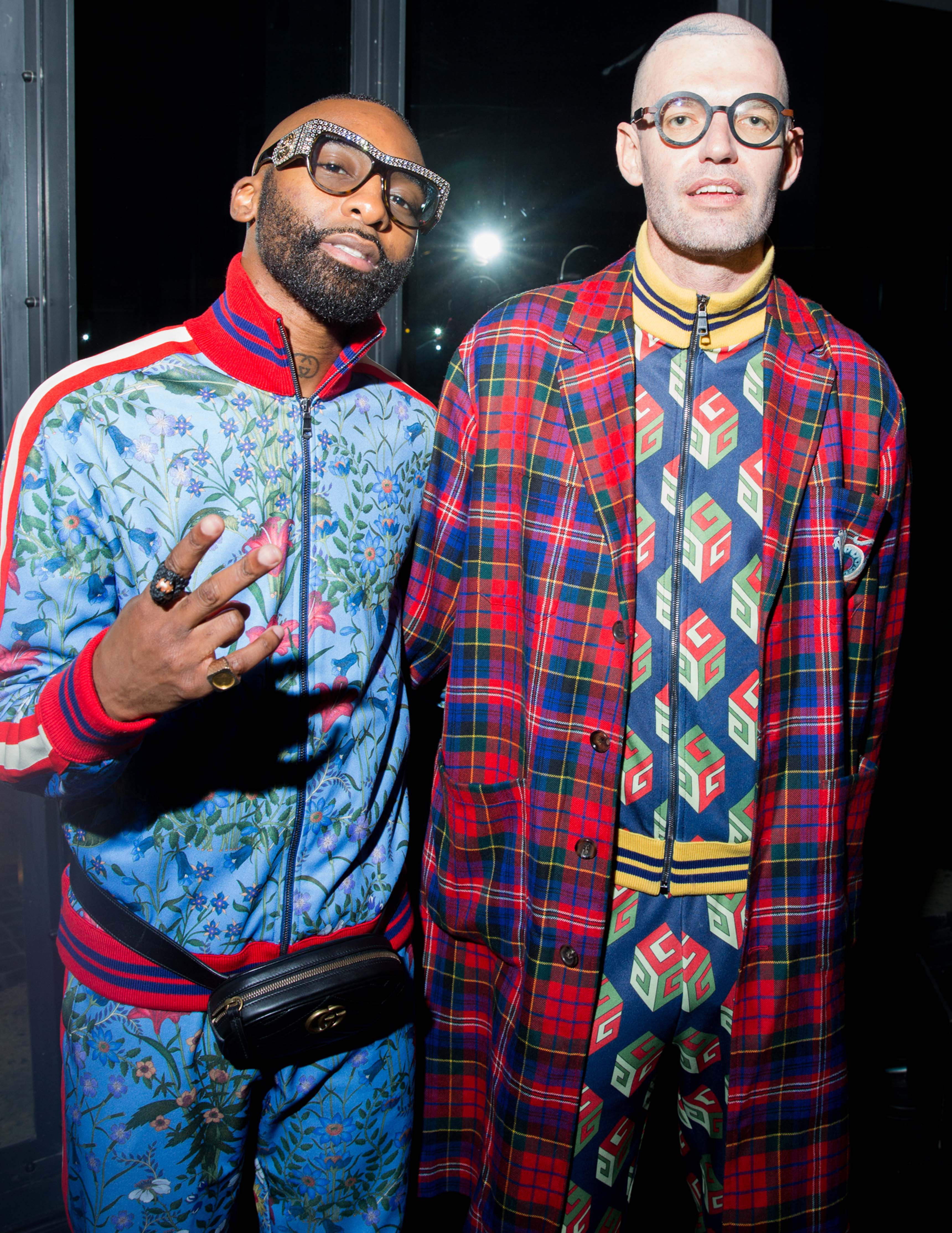 Riky Rick wore a Gucci Fall Winter 2017 azure macro new flora printed technical jersey zipped jacket and an azure macro new flora printed technical jersey jogging pants, a Pre Fall 2017 belt bag in black matelassé chevron leather with GG detail, and a Cruise 2017 leather sole moccasin in black leather with horsebit and Union Jack detail. Louw Kotzewore a Pre Fall 2017 royal bluette technical jersey zipped jacket with GG Wallpaper print and a royal bluette technical jersey jogging pants with GG Wallpaper print, a Pre Fall 2017 flare madras coat with embroidery detail, and Brixton mini GG wallpaper shoes.