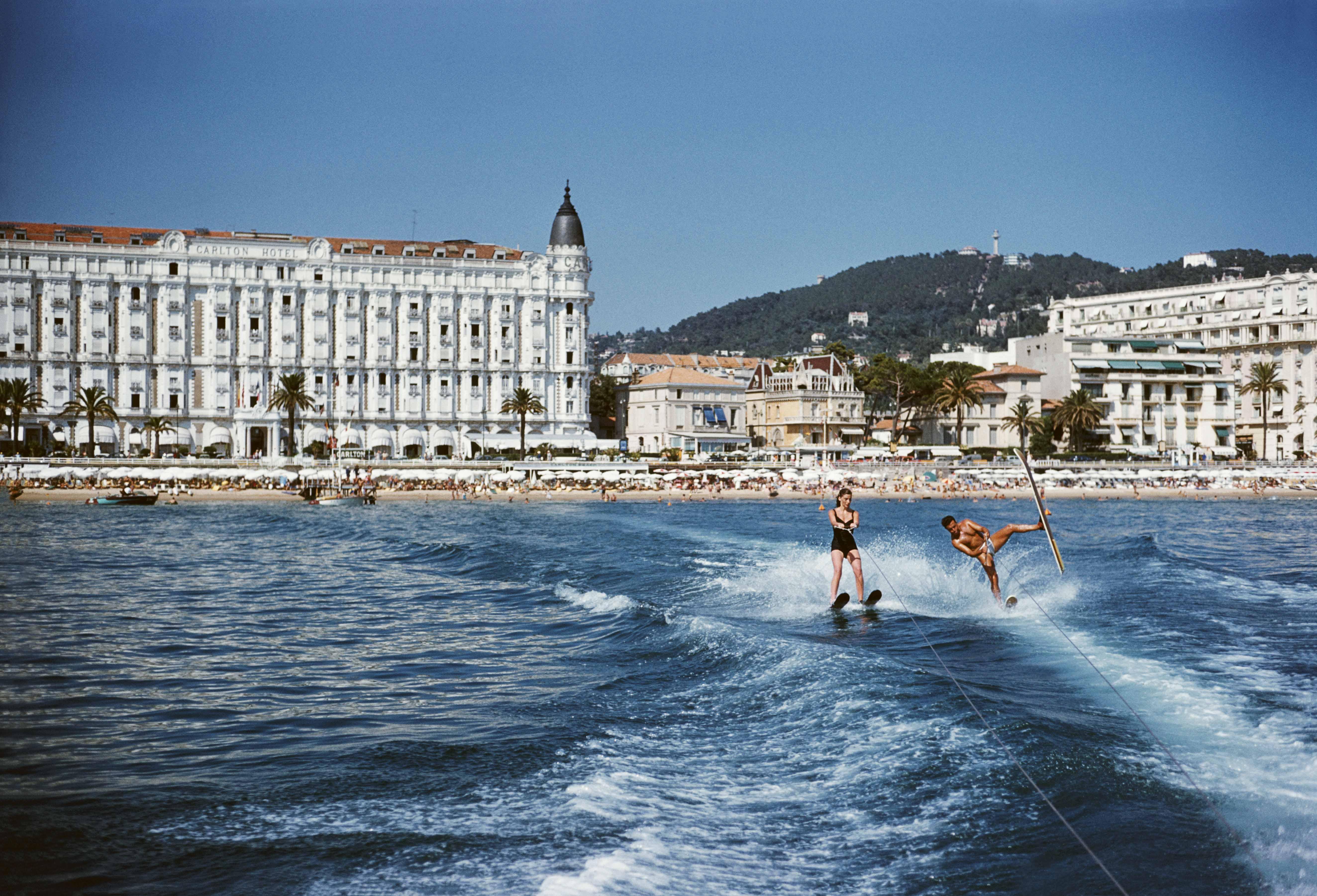 "Slim Aaron, ""Vacanciers en train de faire du ski nautique en face de l'hôtel Carlton"" (1958)."