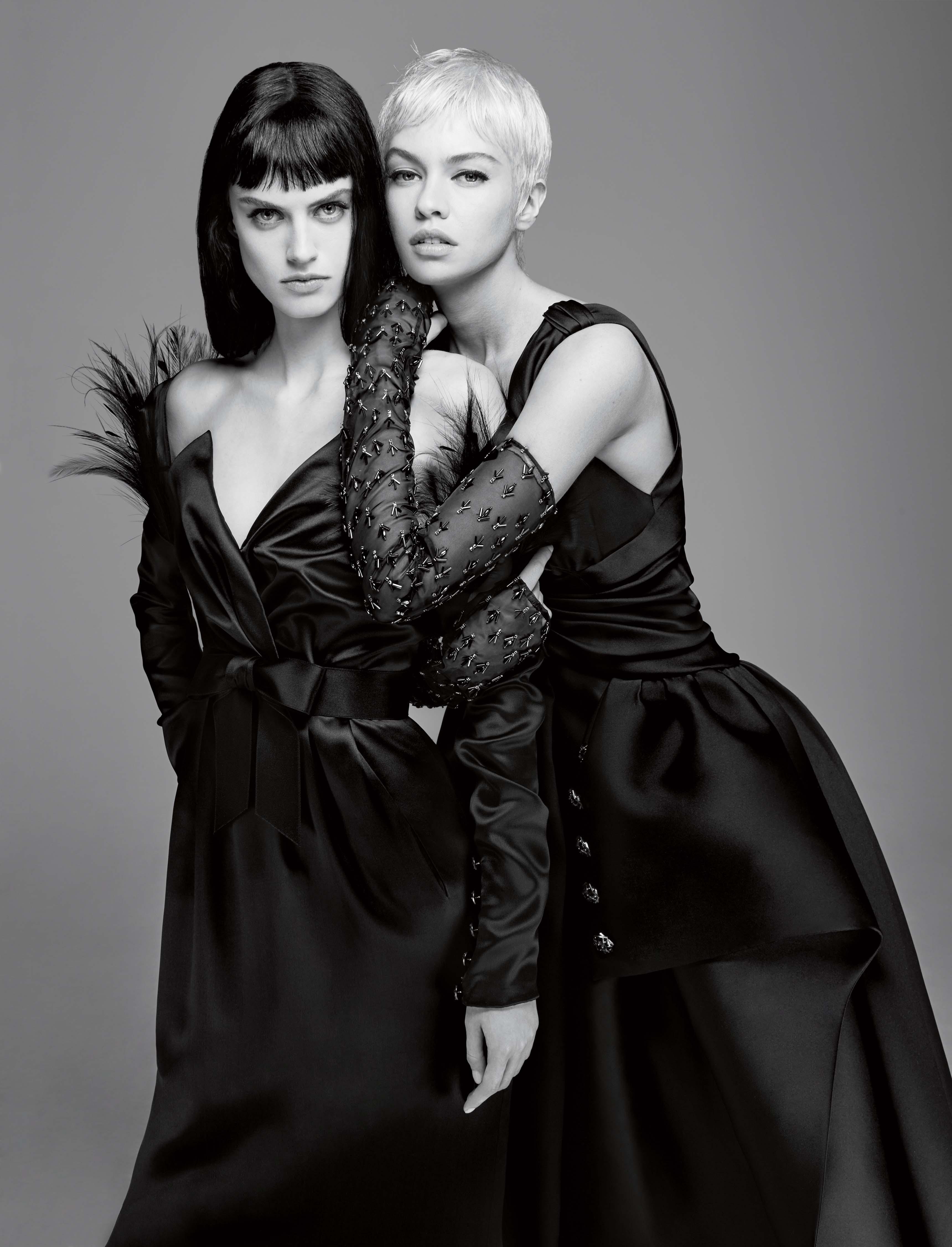 Devant : robe bustier en satin double face à épaulettes brodées de plumes, CHANEL HAUTE COUTURE. Derrière : robe longue en satin double face et mitaines strassées, CHANEL HAUTE COUTURE.