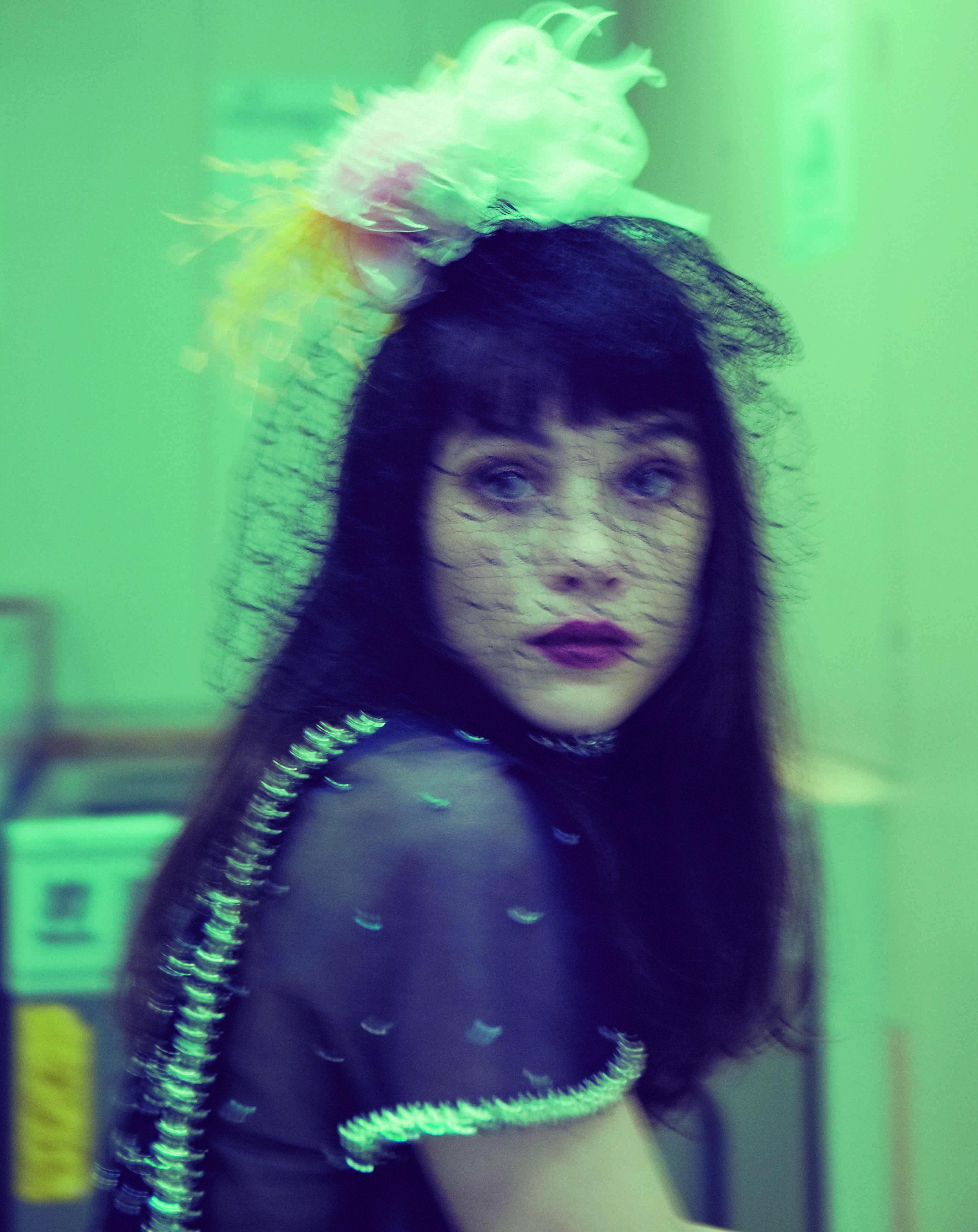 Àstrid Bergès-Frisbey porte une robe longue brodée ornée de boutons bijoux, un tee-shirt à manches courtes en tulle de soie brodé au plumetis et une coiffe à voilette en dentelle ornée de fleurs, CHANEL HAUTE COUTURE.
