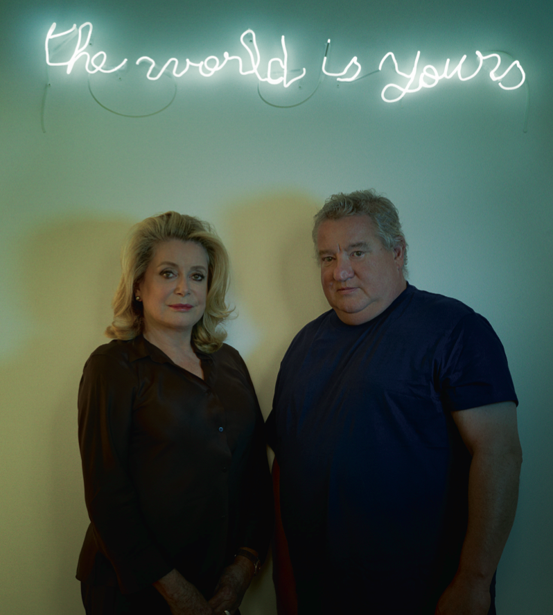 Catherine Deneuve et Claude Lévêque à la galerie Kamel Mennour à Paris, sous un néon de l'artiste, The World is Yours, (2013), néon blanc, 19 x 116 cm (©ADAGP Claude Lévêque).