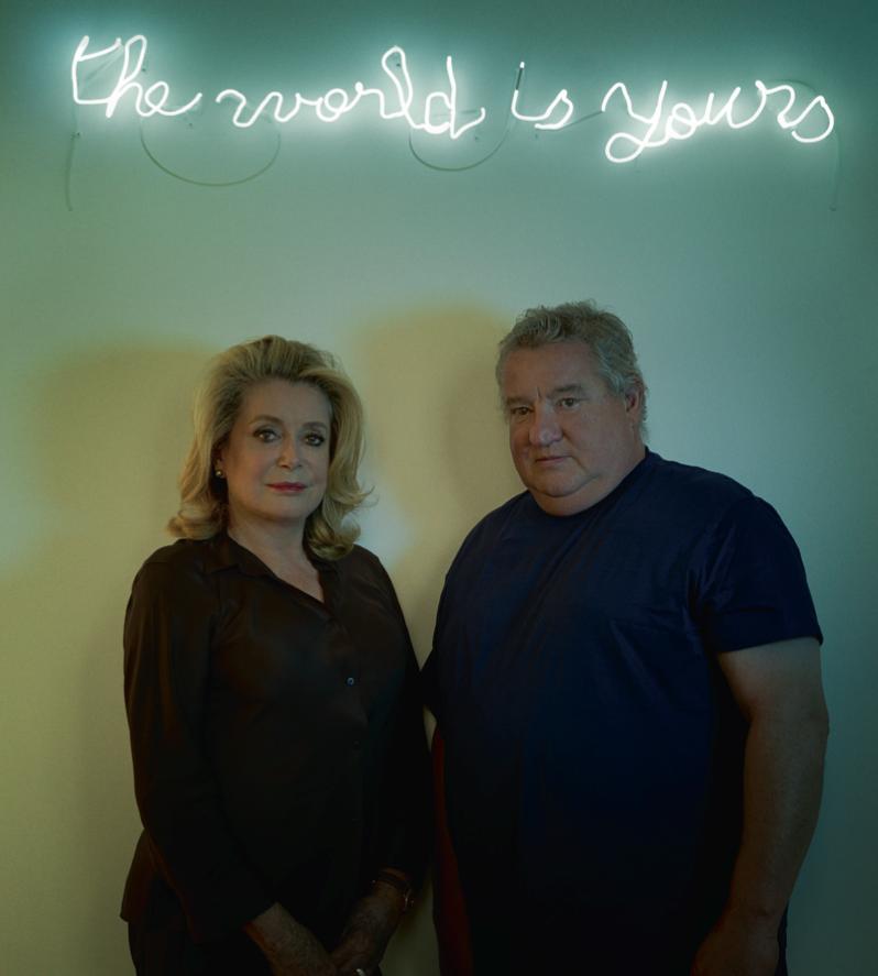Catherine Deneuve et Claude Lévêque à la galerie Kamel Mennour à Paris, sous un néon de l'artiste, The World is Yours, (2013), néon blanc, 19 x 116 cm (©ADAGP Claude Lévêque).