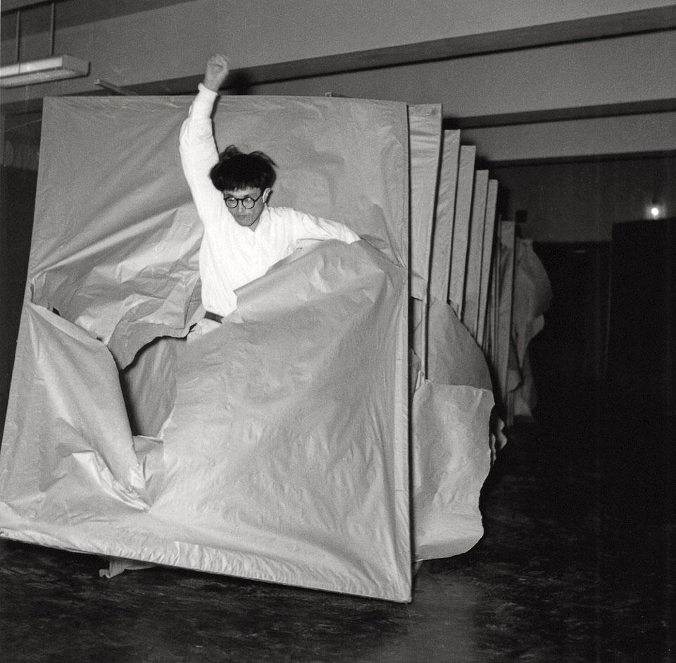 """Saburō Murakami traverse les écrans de papier lors de la deuxième exposition """"Gutaï"""" présentée à Tokyo en 1956."""