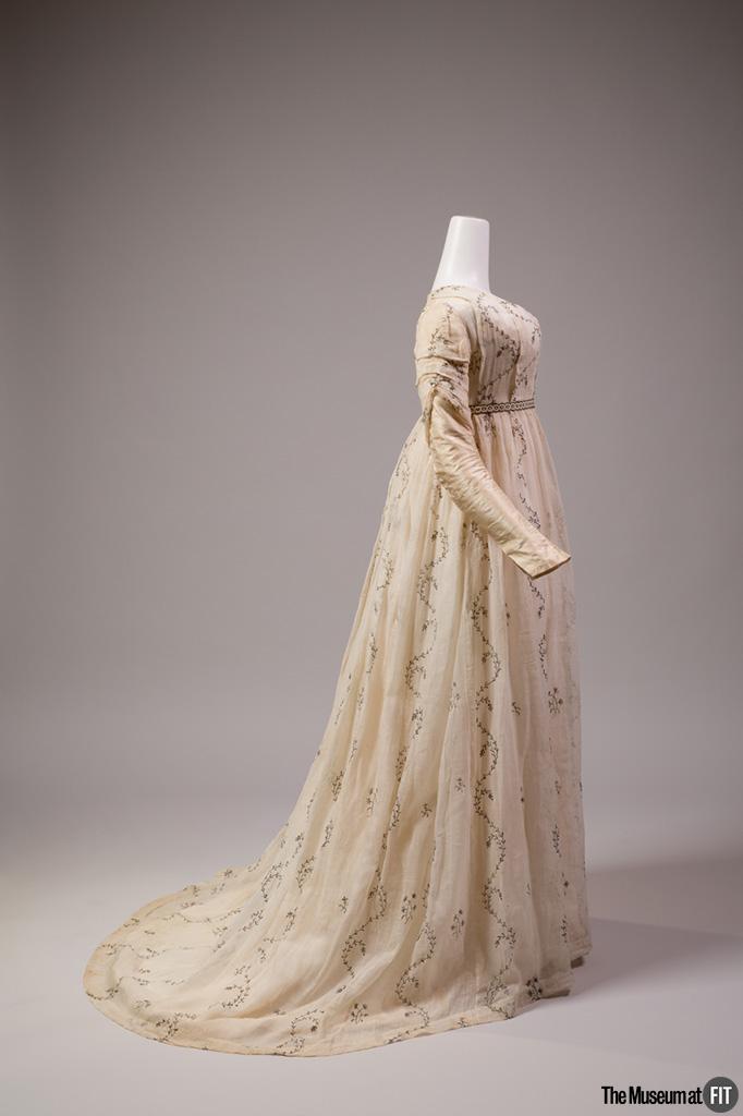 """Robe ronde en """"mousseline argentée"""" de coton blanc brodée de fil argenté et manches en taffetas de soie, datant de 1795-1800."""