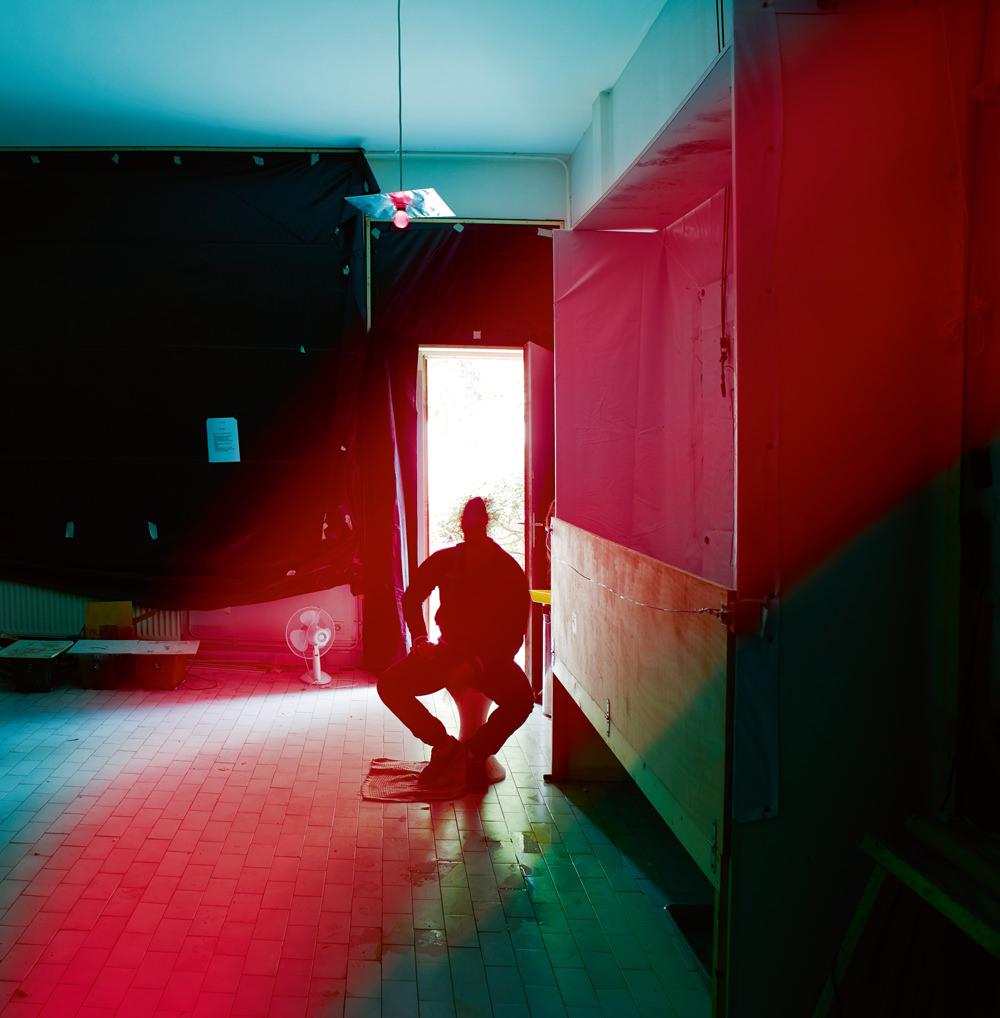 Mohamed Bourouissa, photographié dans son atelier de Gennevilliers. La première pièce a été transformée en chambre noire afin d'effectuer des tirages photographiques sur des carrosseries de voiture, en vue de son exposition à la galerie Kamel Mennour.