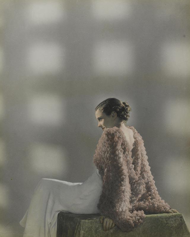 """Dora Maar, photographie de mode, """"Sans titre"""" [mannequin assise de profil en robe et veste de soirée] (vers 1932-1935). Épreuve gélatino-argentique rehaussée de couleurs."""