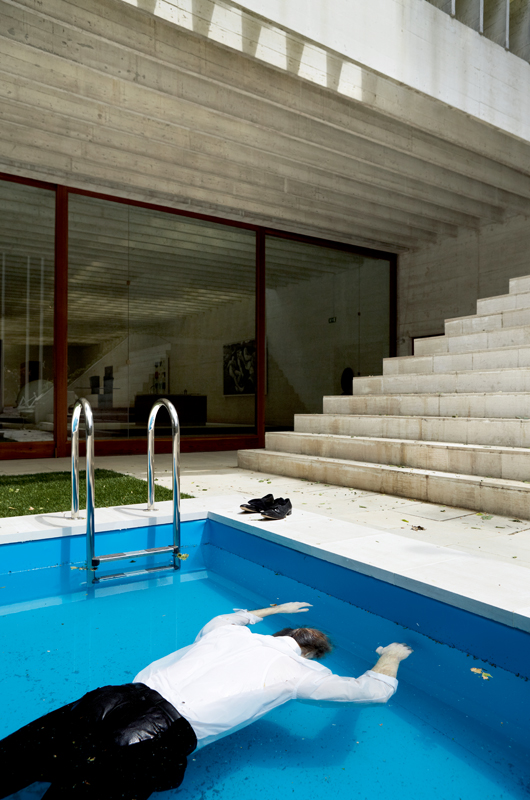 """Death of a Collector"" (2009). Swimming Pool, Silicone Mannequin, Rolex Watch, Marlboro Cigarette Pack, Clothes and Shoes, 100 x 600 x 200 cm. This work was presented at the Venice Biennale in 2009."