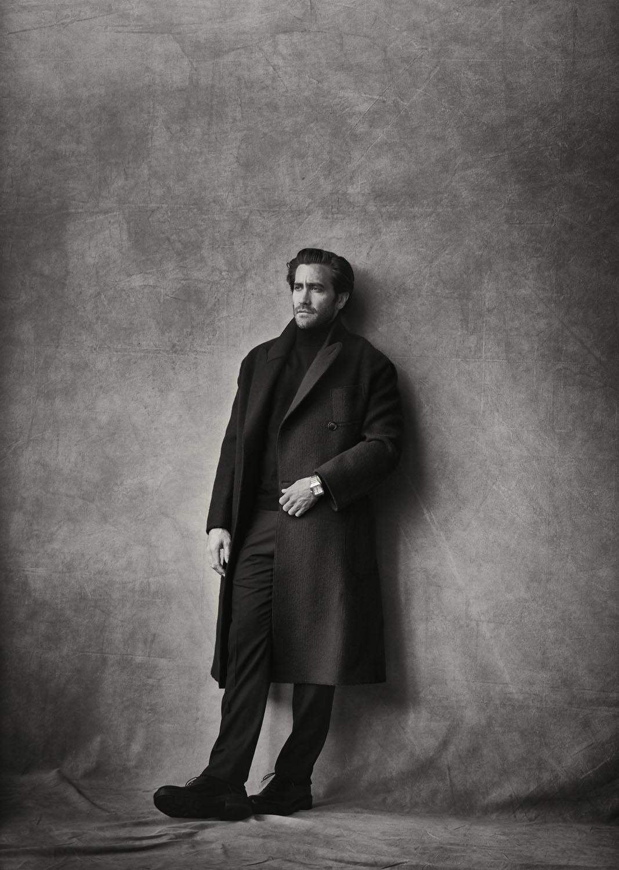 """Jake Gyllenhaal porte un manteau croisé en laine et cachemire, un pull en mérinos, un pantalon en laine et des derbys Giorgio Armani, et une montre """"Santos de Cartier"""", Cartier."""