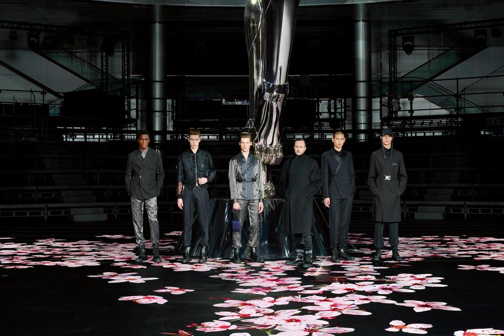Kim Jones photographié à Tokyo avec les mannequins de son défilé pre-fall 2019, devant une sculpture de Hajime Sorayama.