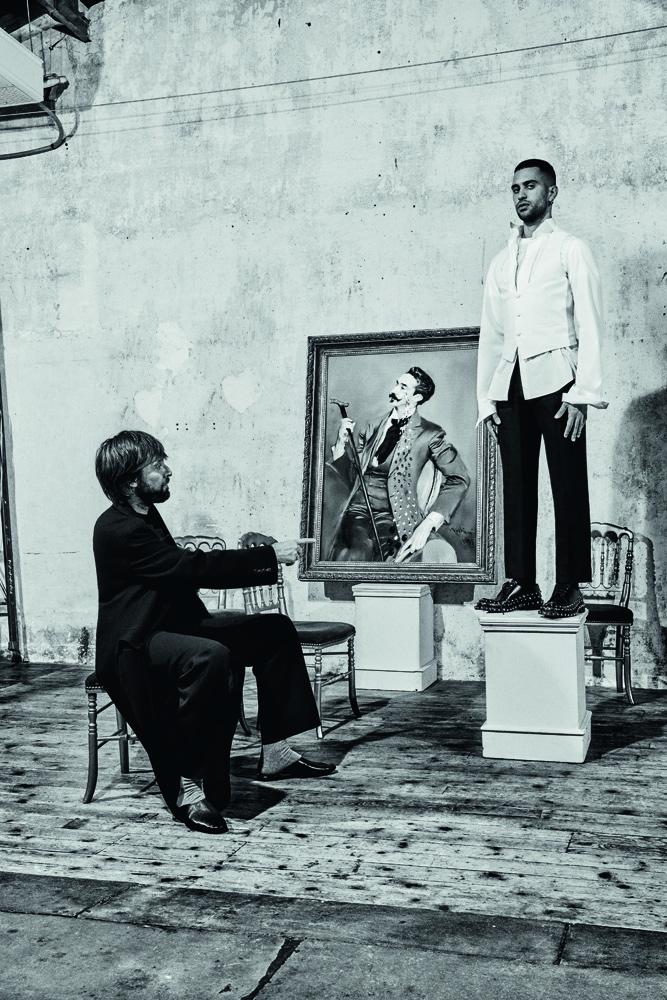 Mahmood est habillé en Prada. Canne, Galerie Fayet. Gants, Agnelle. Francesco Vezzoli porte un manteau en laine, un pull en cachemire et un pantalon de laine, Prada, et des slippers, Charvet.