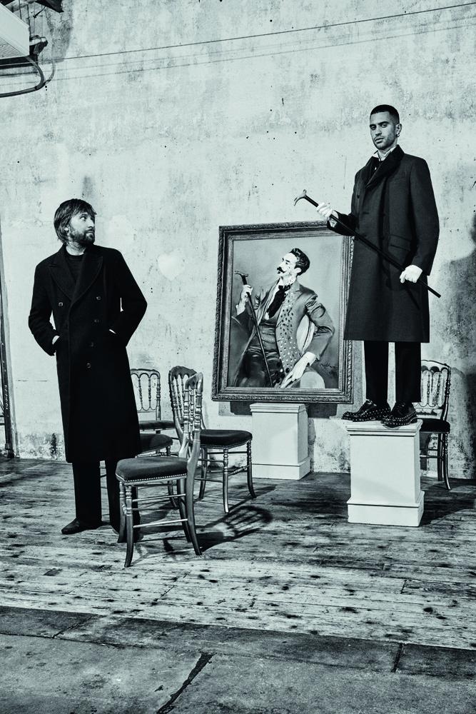 Mahmood est habillé en Prada. Canne, Galerie Fayet. Gants, Agnelle. Francesco Vezzoli porte un manteau en laine, un pull en cachemire et un pantalon de laine, Prada, et des slippers, Charvet. ASSISTANTE DIRECTION ARTISTIQUE : DARIA DI GENNARO. STYLISTE : SUSANNA AUSONI. COUTURIER : MIKOLAJ SOKOLOWSKI. COIFFURE : OLIVIER DE VRIENDT CHEZ THE WALL GROUP. MAQUILLAGE : WILLIAM BARTEL CHEZ ARTLIST PARIS. CONSULTANT ARTISTIQUE : LUCA CORBETTA. SET DESIGN : FILIPPO BISAGNI. ASSISTANT PHOTOGRAPHE : LUCA GALVAGNI. OPÉRATEUR DIGITAL : ANDREA VILLA (DIGITAL AREA)