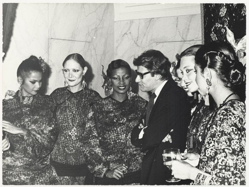 Yves Saint Laurent en 1977, entouré de ses mannequins, lors de la soirée organisée pour le lancement français du parfum Opium, 5, avenue Marceau, à Paris.