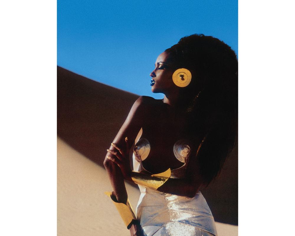"""ERG MEHEDJEBAT (SAHARA ALGÉRIEN), 1985. Iman Abdumajid en """"Seins d'or massif"""" de Mugler"""