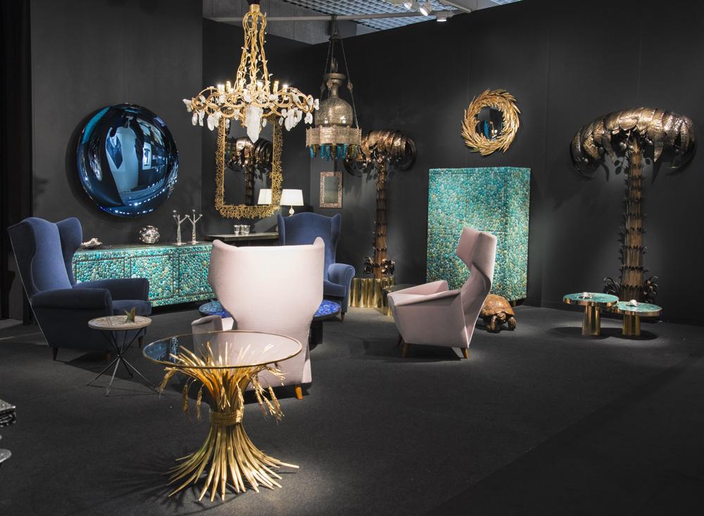 """Vue du stand de Maison Rapin, avec le miroir """"Epis de blé"""" et le lustre """"Ruban"""" de Robert Goossens, ainsi que des meubles de Kam Tin."""