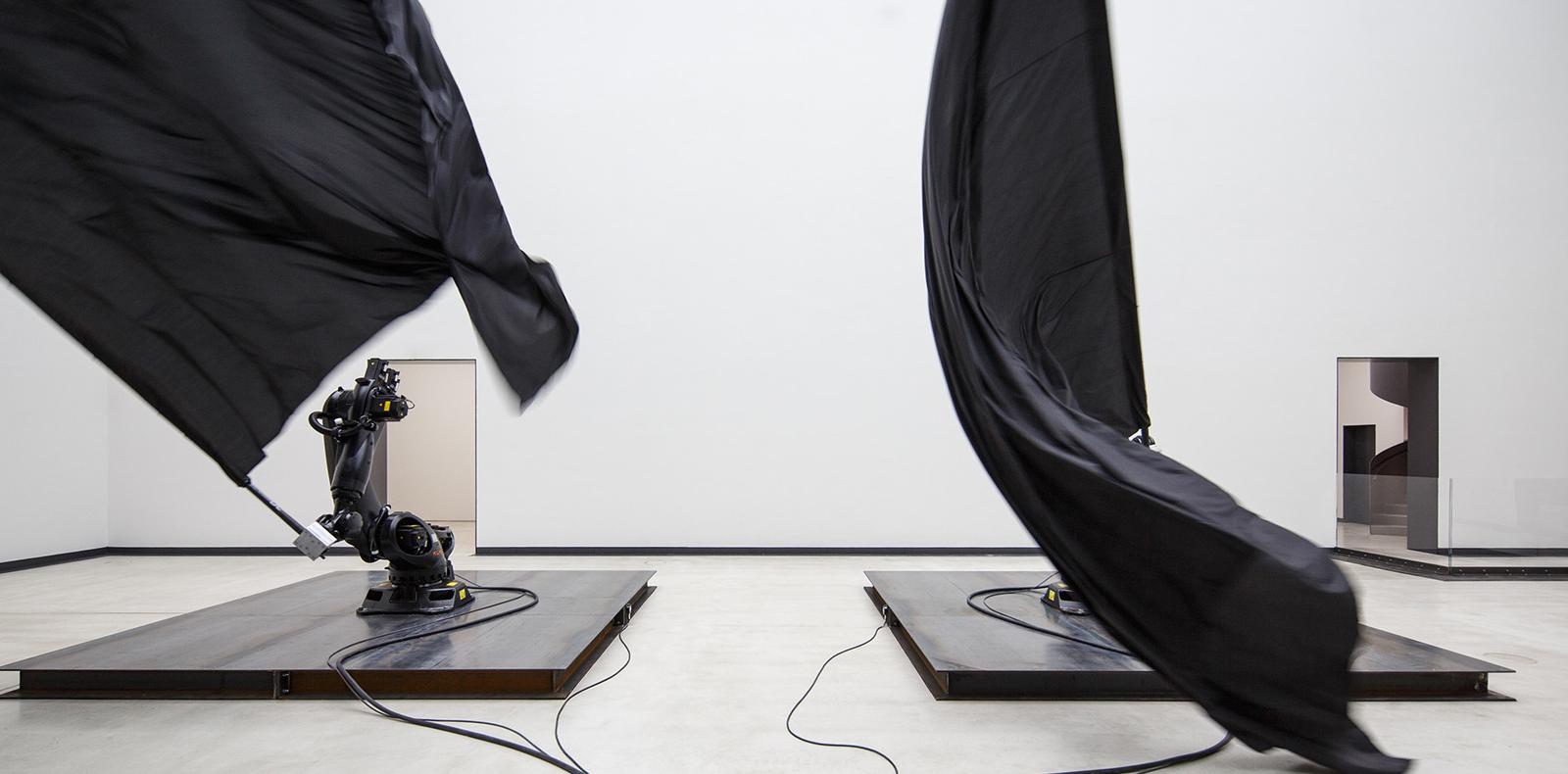 Black flags (2014). Robots industriels readymade, drapeaux de soie, mâts de fibres de carbone, plaques d'acier de dimensions variables.