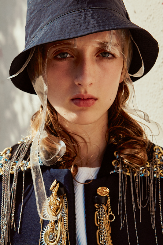 Wool and silk jacket embroidered with chains and pearls, and woolen top, LOUIS VUITTON. Bob, LACOSTE. Hat, MAISON MARGIELA.