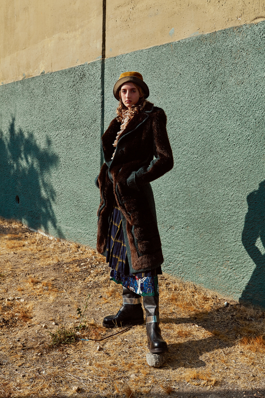 Imitation fur coat in mohair and cotton, ACNE STUDIOS. Ruffled cotton blouse, ZIMMERMANN. Checked wool skirt, CARVEN. Printed silk skirt, MSGM. Bob, LACOSTE. Boots, CALVIN KLEIN.