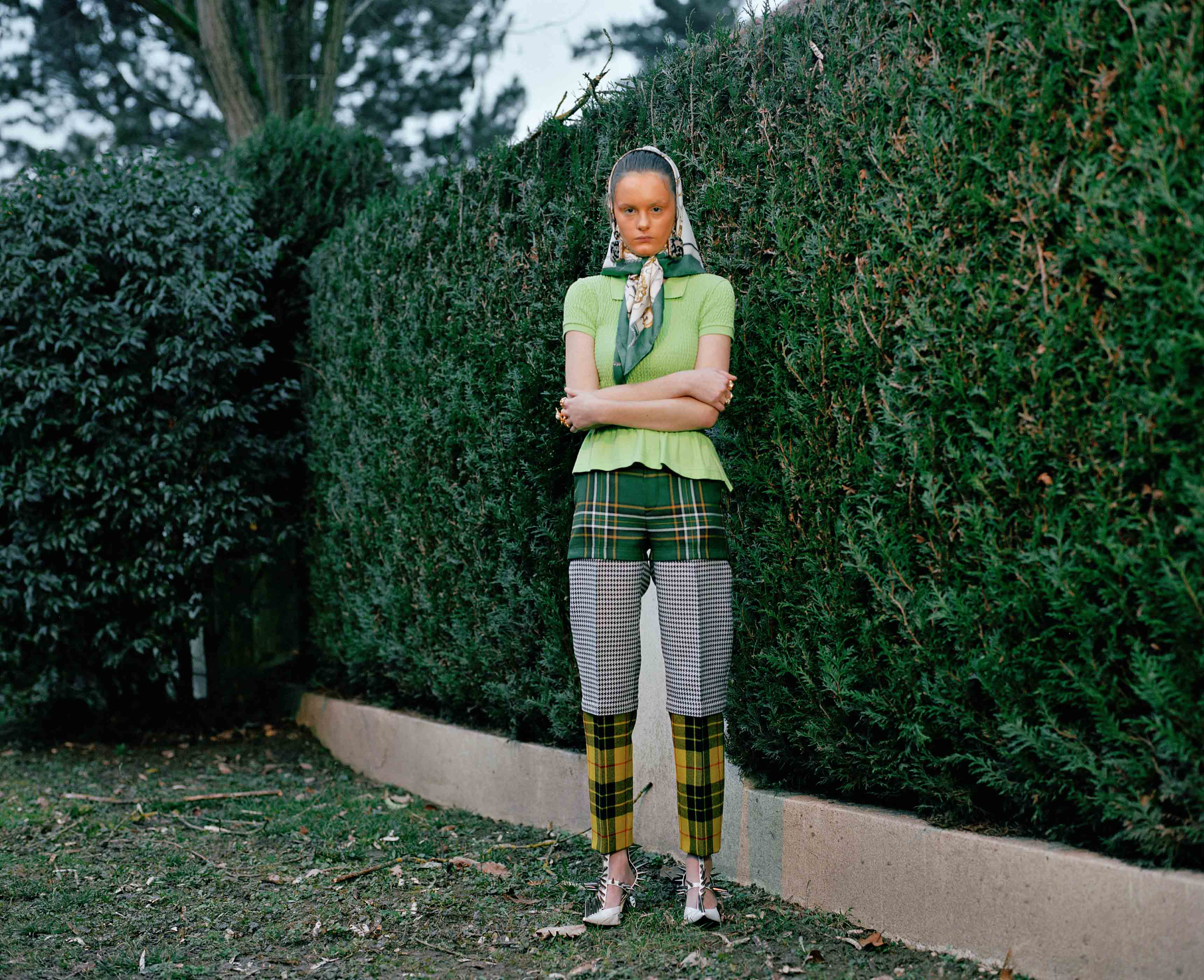 Cotton polo shirt, zip trousers with tartan woolen yokes, earrings and stilettos, BALENCIAGA. Vintage scarf, HERMÈS.