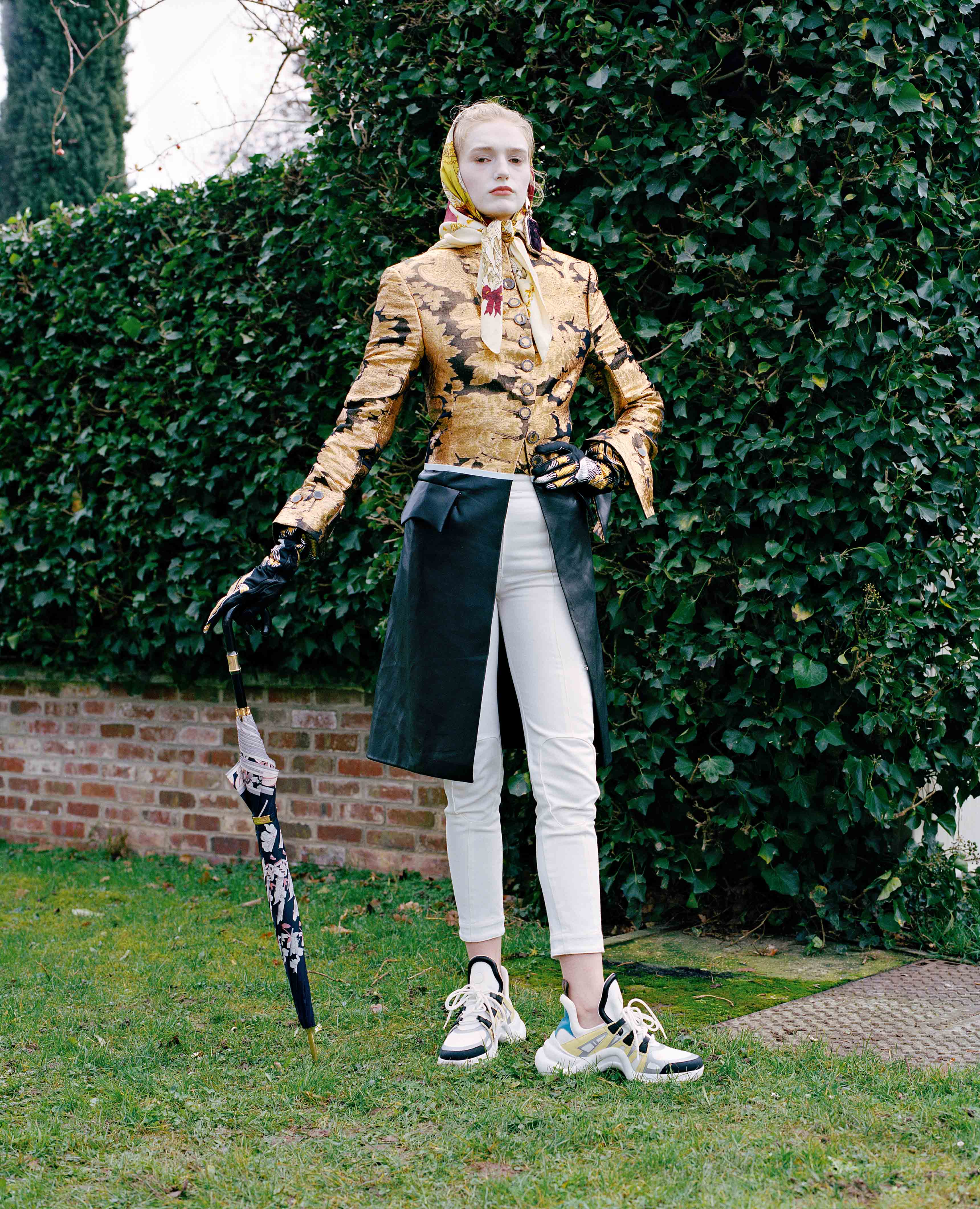 Silken embellished redingote, cotton trousers and snearkers, LOUIS VUITTON. Gloves, ROCHAS. Earring, BALENCIAGA. Vintage scarf, HERMÈS. Umbrella, LÉONARD.