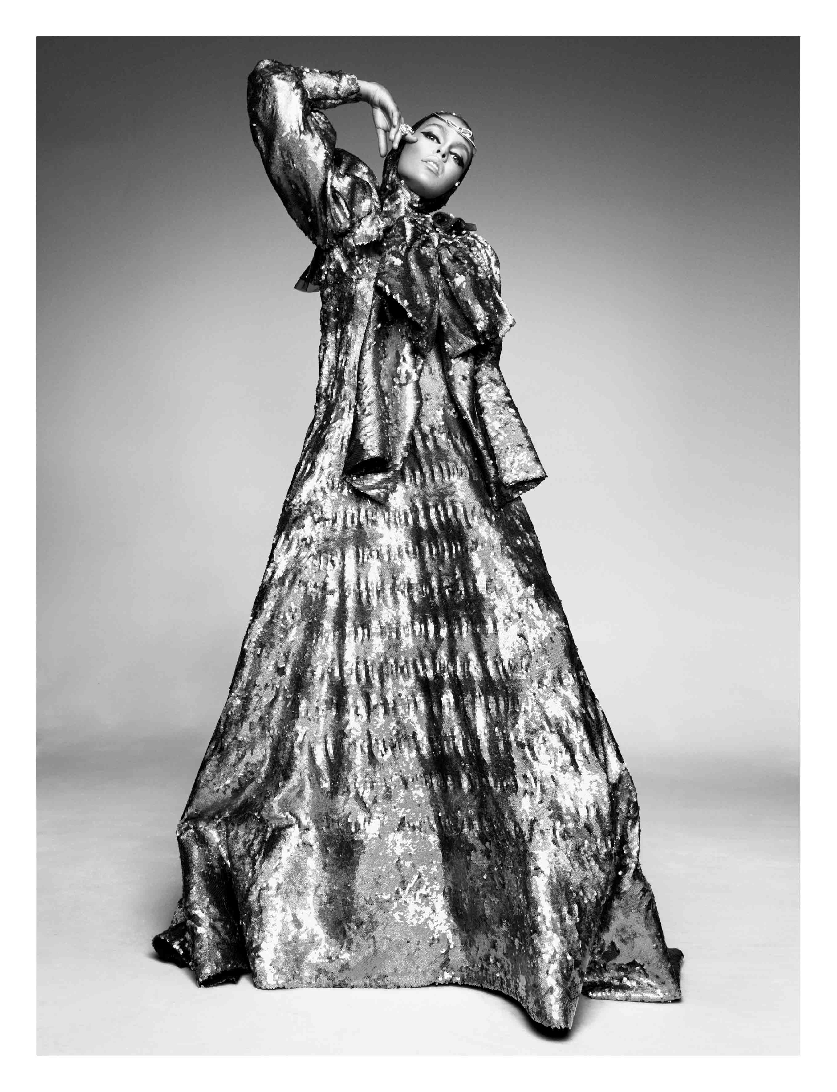 """Longue robe en soie entièrement rebrodée de paillettes, GUCCI. Sur la tête : collier """"Ruban"""" en or blanc et diamants, CHANEL JOAILLERIE. Bagues """"Gourmande Pastel"""" en or, diamants et aiguemarine, DIOR JOAILLERIE."""