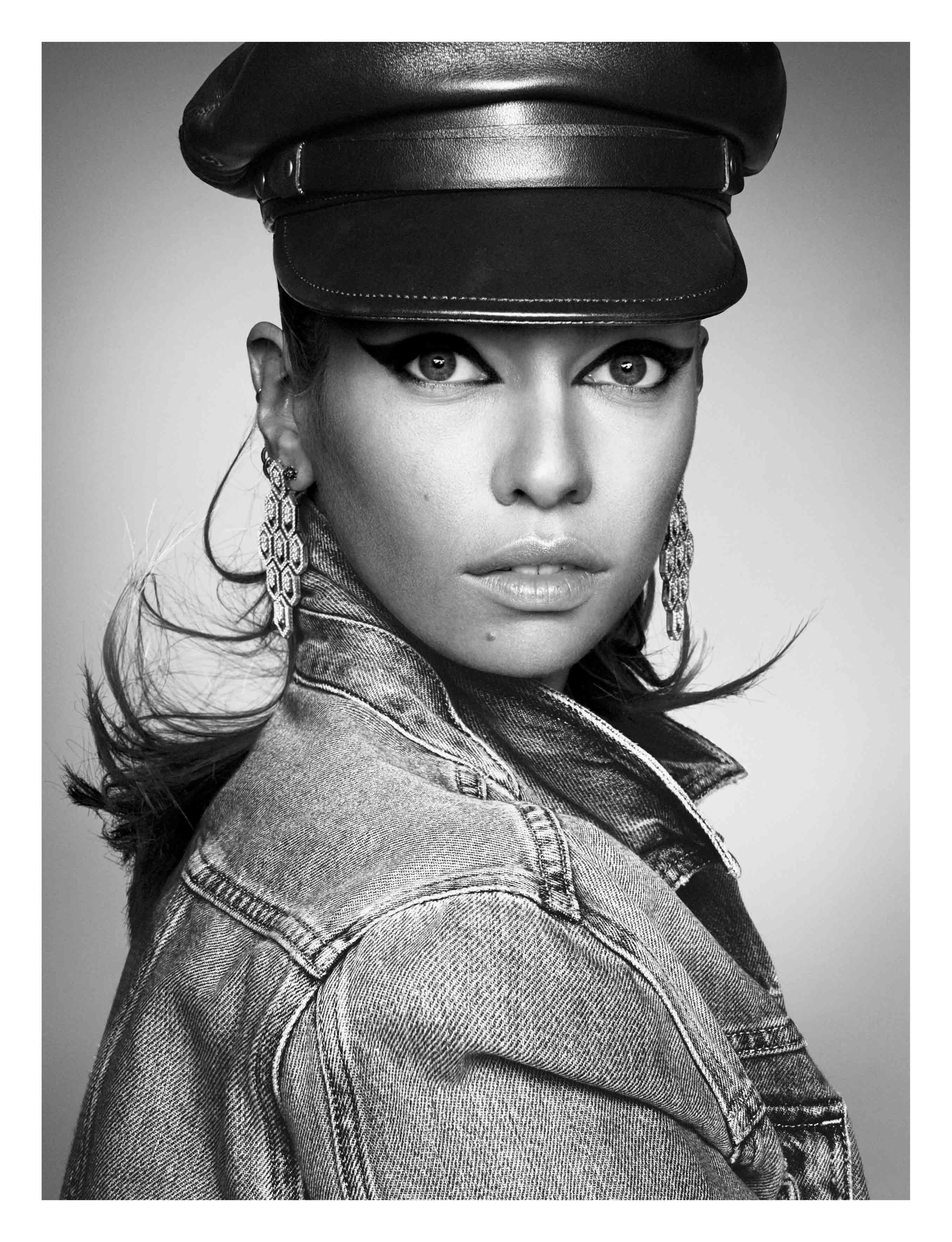 "Veste en denim, GUESS. Casquette, DSQUARED2. Boucles d'oreilles ""Serpenti"" en or blanc et diamants, BULGARI."