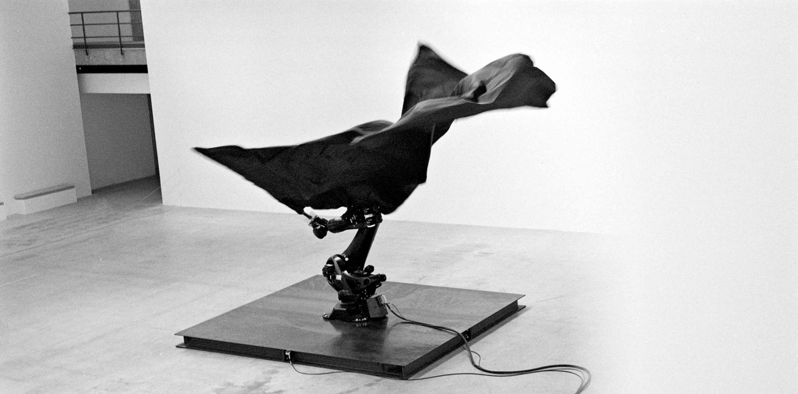 """""""Black Flags"""" (2014) de William Forsythe. Robots industriels ready-made, drapeaux en soie, mâts en fibre de carbone et plaques en acier, dimensions variables."""
