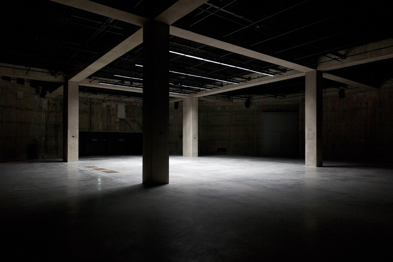 """Les Tanks dans les soubassements accueillent une programmation de performances et de vidéos. © Tate Photography   L'ART AU MILIEU DES CUVES DE FIOUL   Autre choix audacieux du duo, ériger la nouvelle aile sur les cuves de fioul existantes. Celles-là même qui servaient à alimenter les turbines du hall monumental de la Tate. Ces """"Tanks"""" – espaces de 30 mètresinstallés dans les soubassements – rappellent l'origine industrielle du bâtiment. Leur architecture de béton accueille déjà une superbe programmation de performances et de films, des vidéos oniriques du Thaïlandais Apichatpong Weerasethakul (Palme d'or à Cannes) aux instruments excentriques de Tarek Atoui."""