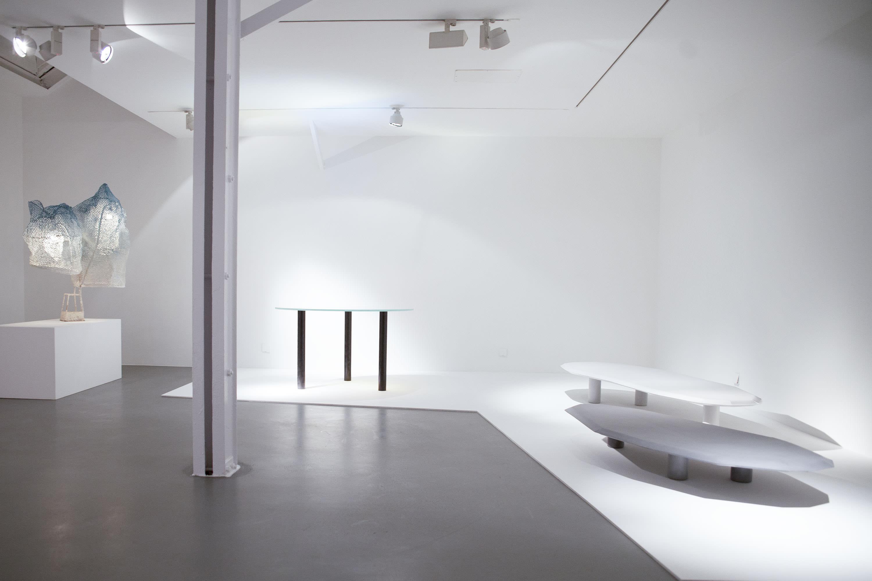 """À gauche : """"Pow Round Table"""", de Robert Stadler (2013), verre et carbone, 75 x Ø 130 cm. À droite : """"Périmètre #01"""", de Normal Studio (2015), béton, 21 x 169,2 x 76,2 cm."""