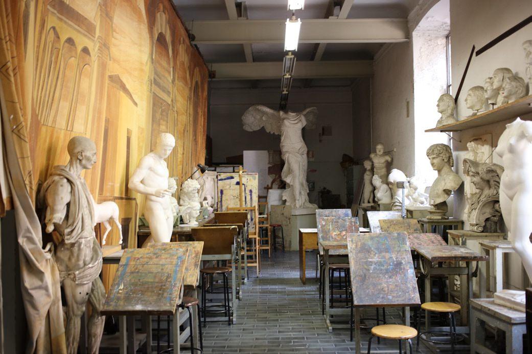 """Depuis sa création, en 1966, dans le Veneto, Bottega Veneta n'a eu de cesse de travailler à la transmission d'un héritage et d'un savoir-faire italien inimitables. Des valeurs qui ne pouvaient qu'entrer en résonance avec l'Académie de Brera. L'école s'enorgueillit à raison de présenter et préserver la culture et l'histoire artistique italiennes depuis plusieurs siècles. Lorsque le Palais Brera est édifié en 1572 (il n'est pas encore question d'académie), il est tout d'abord confié aux jésuites. Son nom doit alors tout à sa localisation, une clairière herbeuse (""""braida"""" en allemand, qui deviendra """"brera"""").   Les lieux s'enrichissent au XVIIesiècle d'un observatoire astronomique, d'un jardin botanique et d'une bibliothèque nationale avant de devenir l'Académie et la Pinacothèque que l'on connaît. C'est le début d'une grande aventure artistique et de la constitution d'une collection de chefs-d'œuvre: Caravage, Léonard de Vinci, Titien, Bellini, Raphaël, Rubens… Une sélection enrichie au XIXe lorsque Napoléon Bonaparte décide d'en faire un musée afin d'y exposer les peintures issues des territoires conquis. Le défilé Bottega Veneta se tiendra d'ailleurs dans les galeries autour de la bibliothèque, au beau milieu des sculptures et peintures qui y trônent encore avec majesté."""