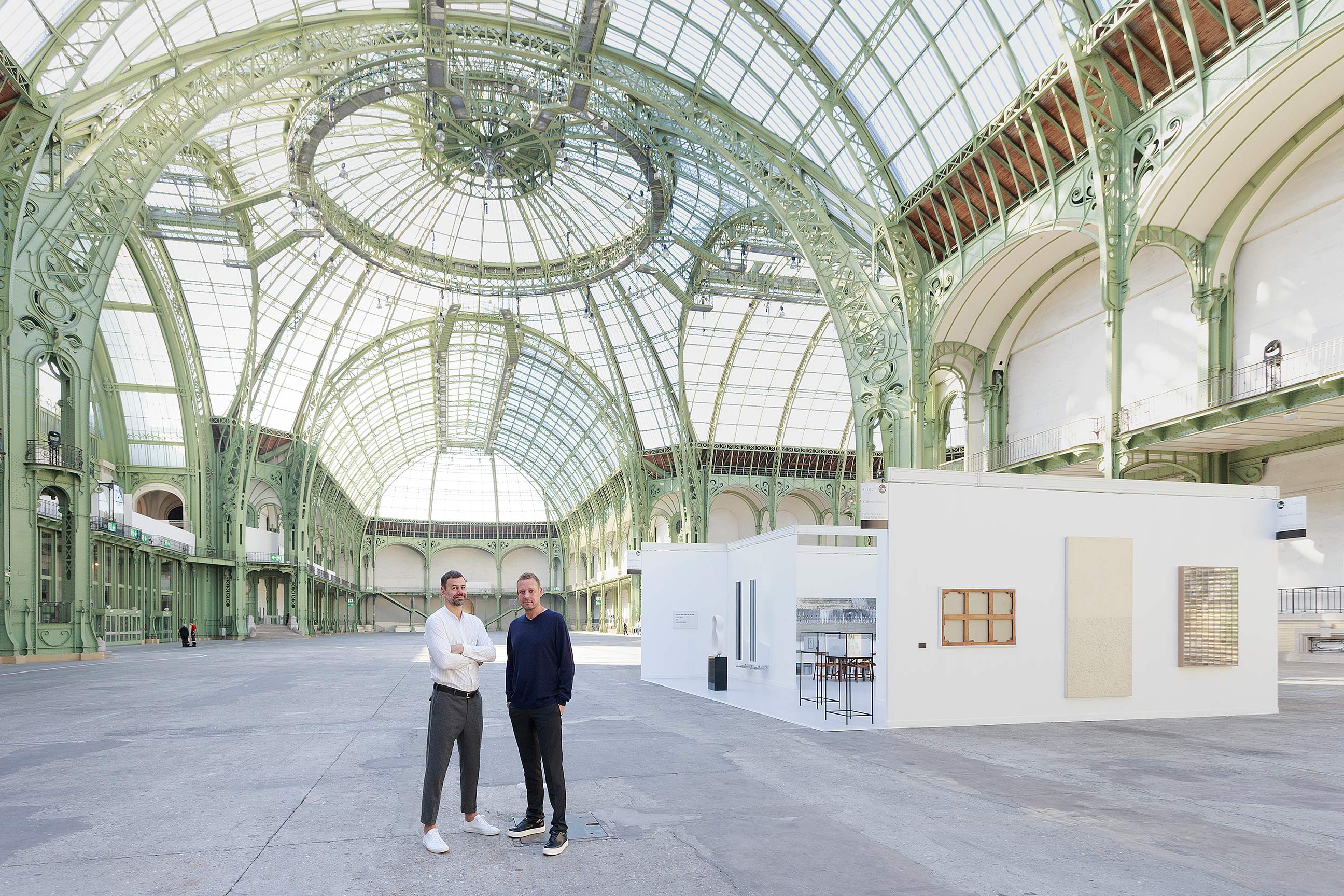 "Elmgreen & Dragset portrait in front of the one-day installation Elmgreen & Dragset présentent la Galerie Perrotin au Grand Palais in Paris on Saturday, September 24th 2016. Photo: Claire Dorn, courtesy Galerie Perrotin   It's always a show of strength when it comes to one of the most important gallery owners in France. And yet the spectacular privatisation on September 24th of the Grand Palais, an architectural gem, obviously costing a pretty penny, shouldn't overshadow the real masterstroke of the day: the artistic duo Elmgreen & Dragset.   In a completely empty Grand Palais the Dane and Norwegian set up the booth to be used by the Perrotin Gallery during the Foire internationale d'art contemporain taking place within the same walls a month later. This ""work stand"" was erected on the exact spot where it will be between October 20th and 23rd. ""The walls, the posters, the lighting elements… everything is an exact replica of what will be built in a month's time. We even had to work with the same companies who work on the FIAC"", the artists tell us. We're reminded of their installation ""Prada Marfa"" (2005), when the duo built a luxury boutique in the middle of the Texan desert. Except that here even the works exhibited are identical to those that will be presented during the fair: pieces by Elmgreen & Dragset of course, but also a KAWS, a Soto, a Murakami, a Veilhan, a JR…      The installation of the stand in an empty Grand Palais radically changes its relationship with space."